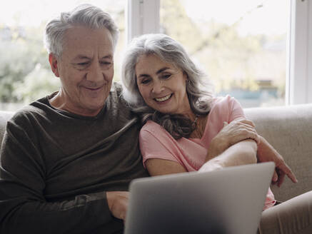 Happy senior couple with laptop relaxing on couch at home - GUSF02989