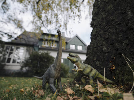 Dinosaur figurines in garden in autumn - GUSF02995