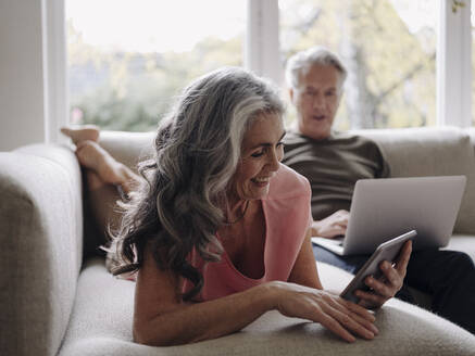 Senior couple relaxing on couch at home using tablet and laptop - GUSF02998