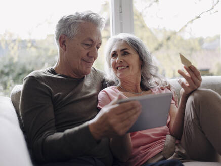 Happy senior couple relaxing on couch at home using tablet for online shopping - GUSF03001