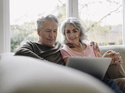 Senior couple with laptop relaxing on couch at home - GUSF03007
