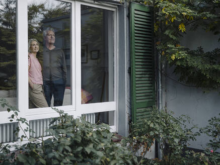 Senior couple behind windowpane of their home looking out - GUSF03013