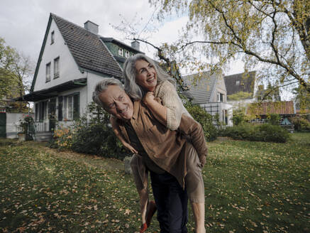 Happy senior man carrying wife piggyback in garden of their home in autumn - GUSF03019