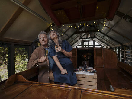 Senior couple having a candlelight dinner on a boat in boathouse - GUSF03022