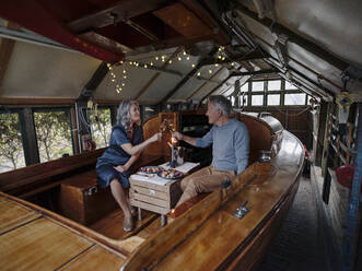 Senior couple having a candlelight dinner on a boat in boathouse clinking champagne glasses - GUSF03025