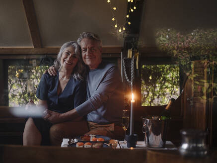 Portrait of senior couple having a candlelight dinner on a boat in boathouse - GUSF03028