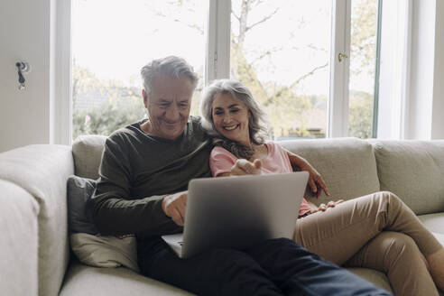 Happy senior couple with laptop relaxing on couch at home - GUSF03037