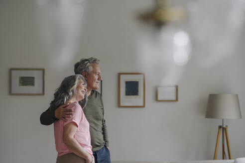 Senior couple standing in living room at home - GUSF03049