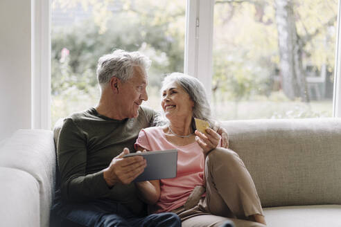 Happy senior couple relaxing on couch at home using tablet for online shopping - GUSF03058