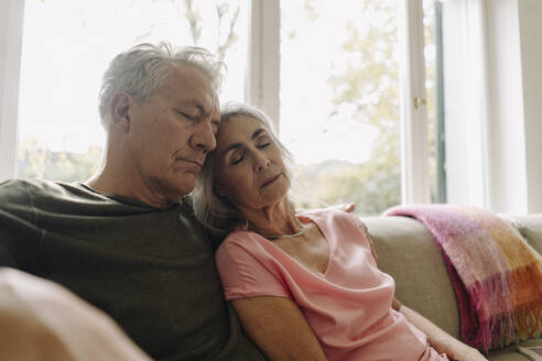 Senior couple napping on couch at home - GUSF03061