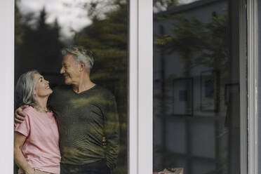 Happy senior couple behind windowpane of their home - GUSF03064
