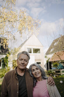 Portrait of senior couple in garden of their home in autumn - GUSF03067