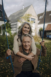 Happy woman embracing senior man on a swing in garden - GUSF03070