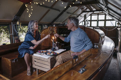 Senior couple having a candlelight dinner on a boat in boathouse clinking champagne glasses - GUSF03079