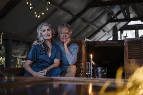 Portrait of senior couple having a candlelight dinner on a boat in boathouse - GUSF03082