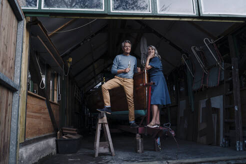 Senior couple in a boathouse with glass of champagne - GUSF03085