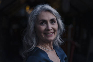 Portrait of a smiling mature woman outdoors at night - GUSF03094