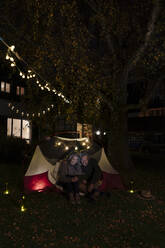 Senior couple with tablet camping in garden of their home at night - GUSF03097
