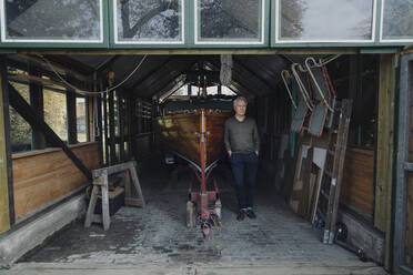 Senior man standing at wooden boat in a boathouse - GUSF03100