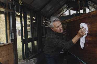 Senior man cleaning wooden boat in a boathouse - GUSF03103