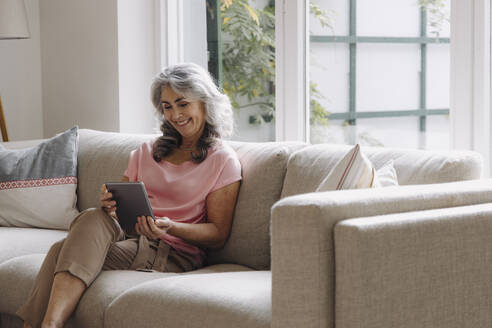 Smiling mature woman using tablet sitting on couch at home - GUSF03106