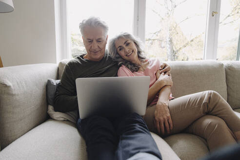 Happy senior couple with laptop relaxing on couch at home - GUSF03112