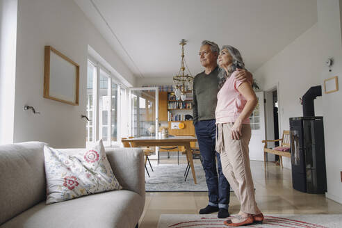 Senior couple standing in living room at home - GUSF03115