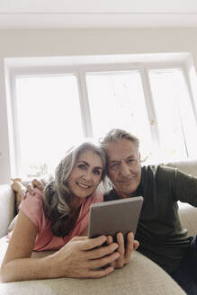 Portrait of happy senior couple relaxing on couch at home with tablet - GUSF03124