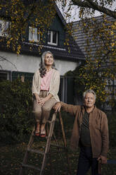 Senior couple with a ladder in garden of their home - GUSF03145
