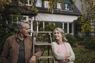 Senior couple with a ladder in garden of their home - GUSF03148