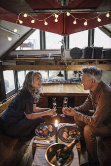 Senior couple having a candlelight dinner on a boat in boathouse - GUSF03154
