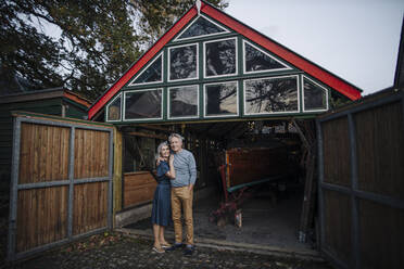 Senior couple standing in front of boathouse - GUSF03157
