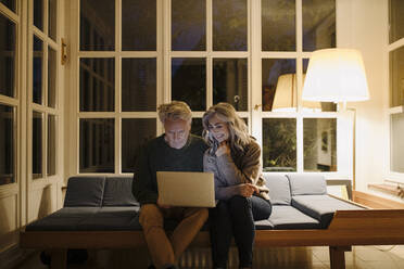 Senior couple using laptop on couch at home at night - GUSF03166