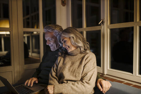 Senior couple using laptop on couch at home at night - GUSF03169
