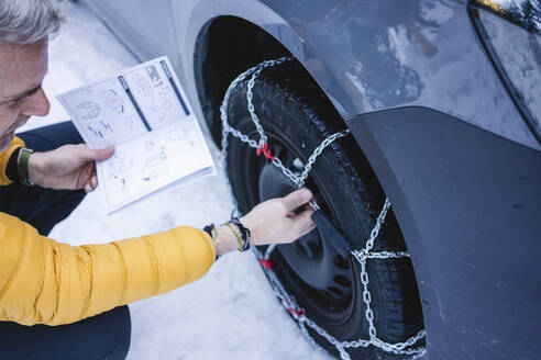 Man putting the snow chains on his car - MRAF00464
