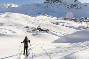 Woman walking with snowshoes in fresh snow in the mountains, Valmalenco, Italy - MRAF00473