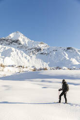Woman walking with snowshoes in fresh snow in the mountains, Valmalenco, Italy - MRAF00476