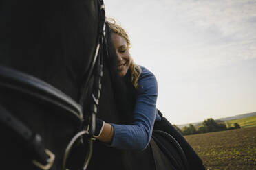 Affectionate woman on horse on a field in the countryside - JOSF04125