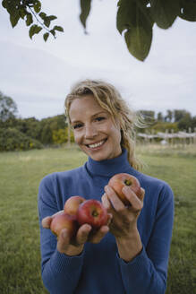 Pirtrait of smiling young woman holding apples in the countryside - JOSF04140