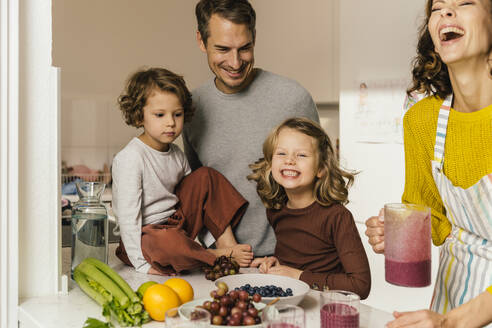Happy family making a smoothie in kitchen - MFF04938