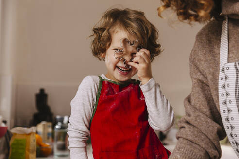Playful girl with her mother holding Christmas cookie cutter in kitchen - MFF04944