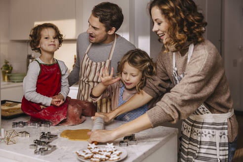 Family preparing Christmas cookies in kitchen - MFF04956