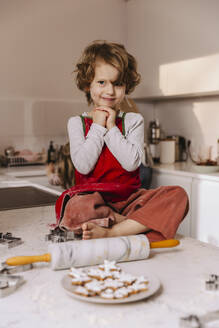 Portrait of smiling girl with Christmas cookies in kitchen - MFF04959