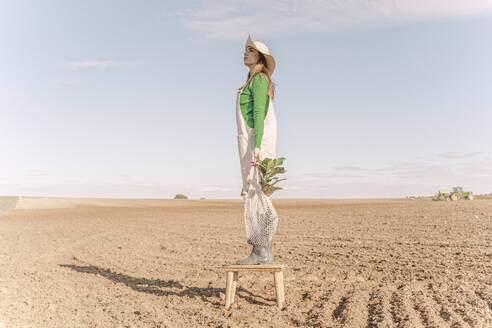 Young woman standing on stool on dry field, carrying plant in a net - ERRF02315