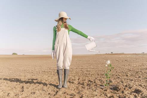 Woamn standing on barren field, watering flower - ERRF02327