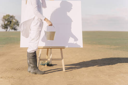 Young woman on dry field, starting to paint on white canvas - ERRF02336