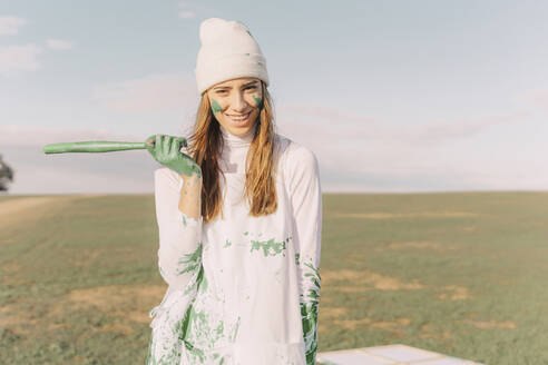 Young woman with green paint on her hands, holding stick, laughing - ERRF02390