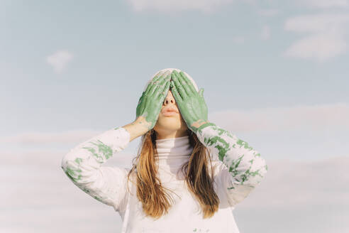 Young woman covering eyes with green hands - ERRF02396