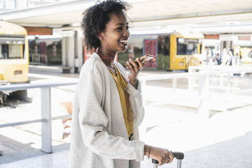 Happy young woman with earphones using smartphone at station platform - UUF19747