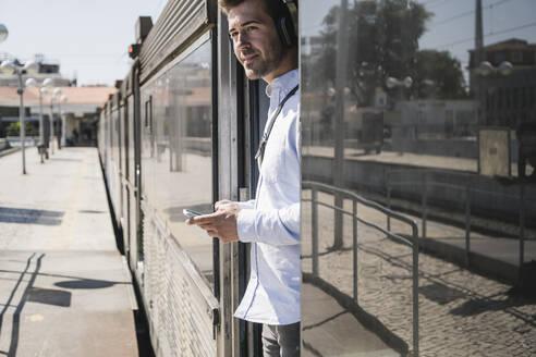 Young man with headphones and smartphone standing in train door - UUF19753